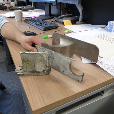 A cracked original welded bracket compared to the machine-from-solid replacement.